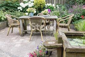 wooden table and chairs in a ornamental garden stock photo istock