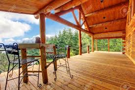 large porch of the log cabin with small table and forest view