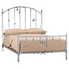 black iron bed frame with curving head board plus curly ornaments