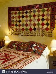 patchwork wall hanging on wall above bed with indian patchwork bed