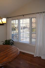 tall white curtains with black metal rod on white wall plus glass
