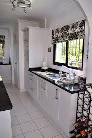 wine kitchen cabinet appliances floral pattern curtain with black quartz countertops