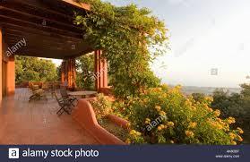 furniture on terracotta flooring on veranda with green climbing