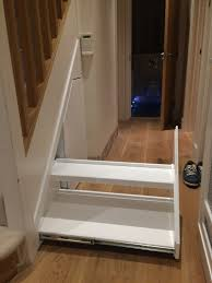 elite interiors london under stairs storage and space saving organised spaces which are fully utilised and give lots of extra hanging space and shelving all neatly hidden away behind shaped doors