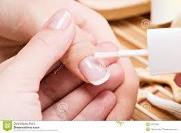 beautician applying nail varnish on a thumbnail stock image
