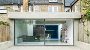 london extension by bureau de change has blue kitchen and white lounge
