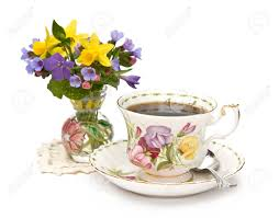 a vase of spring flowers and a teacup on white background stock