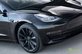 black tesla model 3 blacked out with a custom blue leather