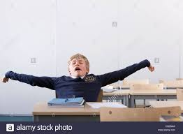 Picture Of Student Sitting At Desk by Male Student In School Uniform Yawning And Stretching At Desk In