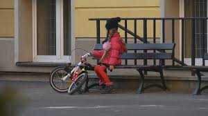 kid is sitting on a bench touching a bicycle have a rest