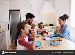 cuisine famille famille disant grace à la table de la cuisine photographie