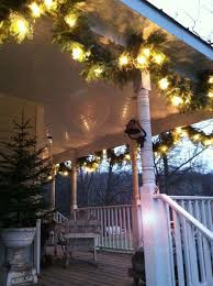 hanging lighted garland on ceiling of covered porch christmas