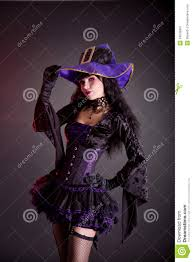 halloween background long cheerful witch in purple and black gothic halloween costume stock