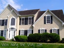 house exterior beige with black shutters and black roof color