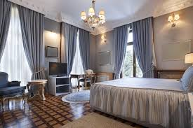 luxury bedroom with light blue curtains and square parquet flooring