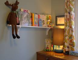 kids room decor with unstained wooden wall bookshelves on green