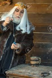 old bearded man wizard in golden crown with long white hair and
