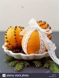 close up of oranges pinned with cloves and wrapped in lace stock