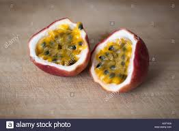 close up of a passion fruit cut in half stock photos close up of fresh passion fruit cut in half on a butcher block stock image
