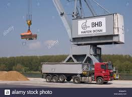 bonn port bulk cargo crane with bucket for sand next to it