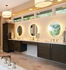 lighted mirror with modern orange county and dark wood bathroom
