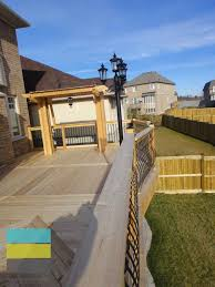 2 level cedar deck with wrought iron railings pergola and stone