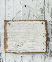 old weathered white wood signboard hanging from an old nail stock