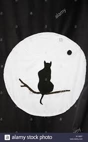 black cat sitting on branch and moon symbol stock photo 121124494