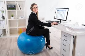 businesswoman sitting on pilates ball using computer in