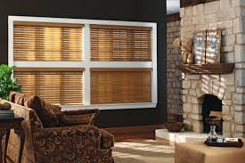 living room with wooden window blinds and dark stone wall