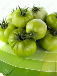 green tomatoes with matching green paint color swatches stock