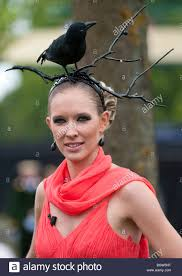 a woman wearing a hat made with a black raven royal ascot stock