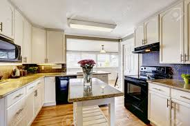 white kitchen with black appliances christmas lights decoration