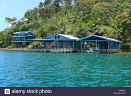 caribbean home and boat house over the water with lush tropical