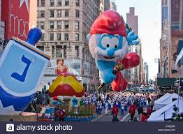 new yorker thanksgiving cartoon papa smurf cartoon character balloon floats past crowds during the