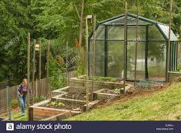 woman walking by her terraced garden and greenhouse in a shady
