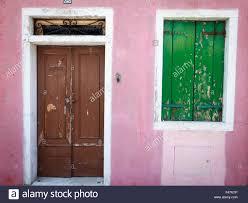 door window pink shutter old fame house blue green brown