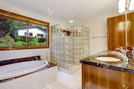 bathroom with glass block screened shower brown cabinet with