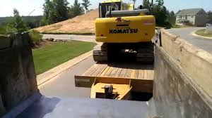 guy rides in bed of dump truck while moving excavator youtube