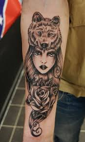 black and gray style forearm tattoo of woman with rose and wolf