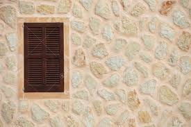 window with closed wooden shutters in a natural stone wall of