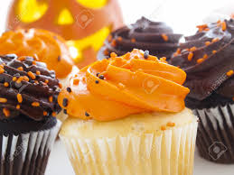 halloween cupcakes with orange and black icing on white plate