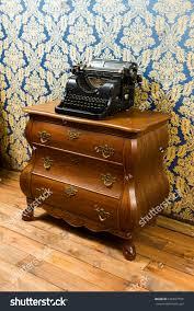 vintage typewriter on wooden bureau stock photo 635827595