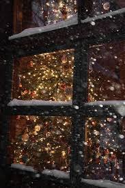 tree lights through snowy window original source not
