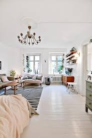 top 25 best cozy studio apartment ideas on pinterest studio scandinavian style studio living white walls white floors black and white area rug chandelier bright open space