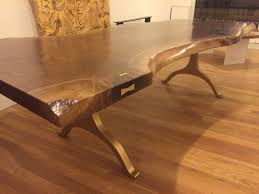 custom live edge table top with steel or brass bowtie inlays by