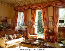 opulent silk drapes on windows in country bedroom with