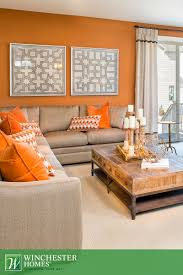 Brown And Blue Living Room by Orange Walls Patterned Artwork And Light Carpets Add To The