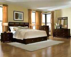 black wooden bed with brown sheet placed on the middle of bedroom