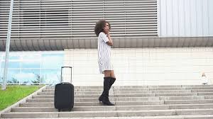 elegant african american woman with luggage at airport white